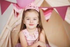 Menina pequena engraçada da princesa do close up na coroa e no vestido cor-de-rosa Fotografia de Stock