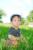 Menina pequena, engraçada que senta-se na grama Imagem de Stock Royalty Free