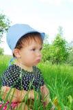 Menina pequena, engraçada que senta-se na grama Foto de Stock Royalty Free