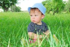 Menina pequena, engraçada que senta-se na grama Imagem de Stock