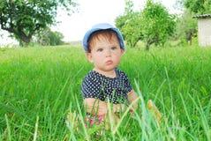 Menina pequena, engraçada que senta-se na grama Imagens de Stock