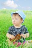 Menina pequena, engraçada que senta-se na grama Foto de Stock