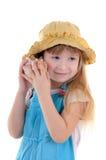 A menina pequena escuta um escudo do mar foto de stock