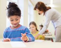 Menina pequena feliz da escola sobre o fundo da sala de aula Imagens de Stock Royalty Free