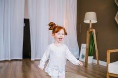 Menina pequena feliz do ruivo que joga na sala grande fotografia de stock
