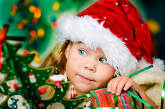 A menina pequena feliz no chapéu de Santa tem um Natal