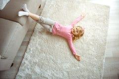Menina pequena feliz que encontra-se no assoalho perto do sofá fotografia de stock royalty free