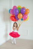 A menina pequena joga com os balões coloridos no estúdio foto de stock royalty free