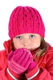 Menina pequena na camisola cor-de-rosa que respira em suas mãos fotografia de stock royalty free