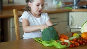 A menina pequena na cozinha que corta acima os brócolis filme