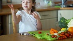 A menina pequena na cozinha que corta acima os tomates de cereja vídeos de arquivo