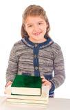 Menina pequena na frente de uma pilha dos livros Fotos de Stock Royalty Free
