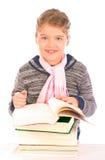 Menina pequena na frente de uma pilha dos livros Imagem de Stock Royalty Free