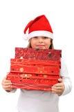 Menina pequena no chapéu de Santa que carreg três presentes fotografia de stock