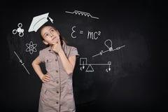 Menina pequena no tampão imaginário da graduação que pensa sobre a escola Fotos de Stock Royalty Free