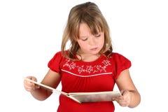 A menina pequena no vermelho lê um livro isolado no branco fotografia de stock
