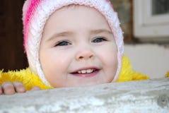 A menina pequena olha para fora atrás de um parapeito Imagens de Stock Royalty Free