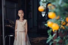 Menina pequena perto de suas casa e árvore alaranjada Foto de Stock