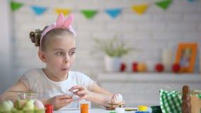Menina pequena que come secretamente o ovo de chocolate, infância, preparação para a Páscoa filme