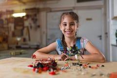Menina pequena que faz um robô fotografia de stock