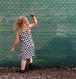 Menina pequena que golpeia em uma cerca verde Imagens de Stock Royalty Free