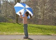 Menina pequena que joga com o guarda-chuva no dia ventoso. Fotografia de Stock