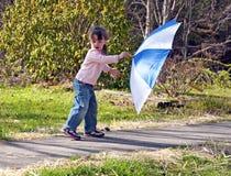 Menina pequena que joga com o guarda-chuva no dia ventoso. Imagem de Stock Royalty Free