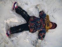 Menina pequena que joga o anjo da neve Imagens de Stock