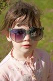 Menina pequena que modela óculos de sol grandes. Imagem de Stock