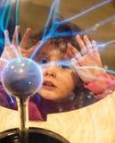 Menina pequena que olha em uma bola do plasma Fotografia de Stock