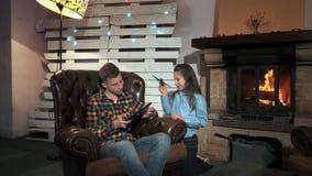 Menina pequena que perturba seu irmão para usar a tabuleta video estoque