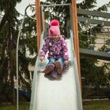 Menina pequena que tem o divertimento nas atrações das crianças Fotografia de Stock