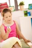 Menina pequena que texting no telefone em casa Fotografia de Stock