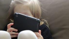 Menina pequena que usa uma tabuleta que senta-se em um sofá vídeos de arquivo