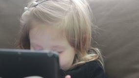 Menina pequena que usa uma tabuleta que senta-se em um sofá filme