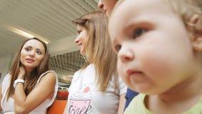 A menina pequena séria do close up olha a câmera com interesse real video estoque