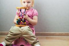 A menina pequena senta-se em um urinol Imagens de Stock Royalty Free
