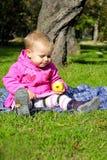 A menina pequena senta-se no glade verde Imagens de Stock