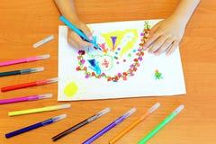 A menina pequena tira penas de feltro A criança mantém uma pena azul de feltro disponivel e tira princesas e flores abstratas Uma imagens de stock royalty free