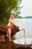 A menina perdeu seu guarda-chuva no dia nebuloso no lago Imagem de Stock