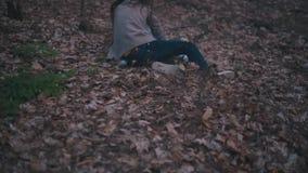 Menina perdida pequena com um lenço brilhante que corre através da floresta escura, é amedrontada e só, cai para baixo, obtém
