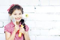 A menina permanece com escova e rolo de pintura à disposicão Foto de Stock Royalty Free