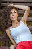 Menina pernudo encantador nova com cabelo encaracolado em uma camisa branca e em um short vermelho que sentam-se nas escadas de m Imagens de Stock Royalty Free