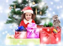 Menina perto da árvore de Natal cercada por presentes Foto de Stock