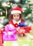 Menina perto da árvore de Natal cercada por presentes Fotos de Stock Royalty Free