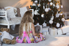 Menina perto da árvore de Natal com presentes e brinquedos, caixas, Natal, ano novo, estilo de vida, feriado, férias, Santa de es Fotografia de Stock Royalty Free