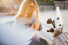 Menina perto da bicicleta motorizada no por do sol fotografia de stock