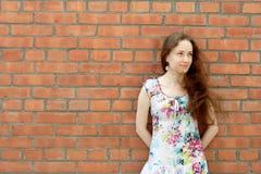 Menina perto da parede de tijolo fotos de stock royalty free