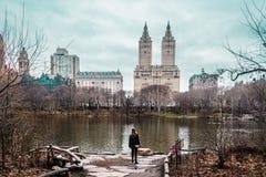 Menina perto das árvores, do rio e das construções no Central Park nos Manh Foto de Stock Royalty Free