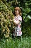 A menina perto de um arbusto de florescência Fotografia de Stock Royalty Free